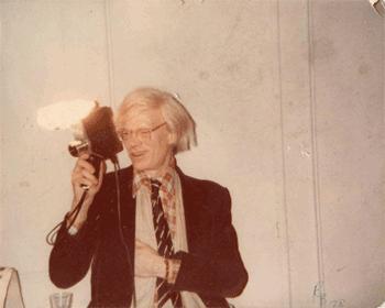 A polaroid photo of Warhol with a night club dance signed by Warhol
